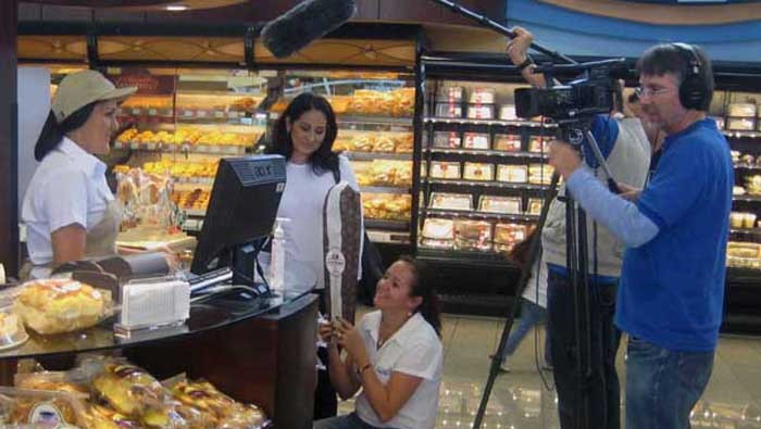 Script girl Marielos Hernández explains to the talent how the bread should come into the shot